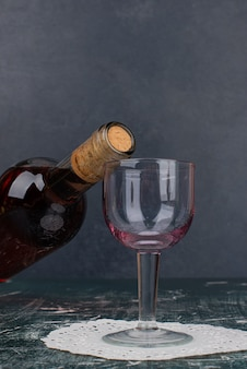 Garrafa de vinho tinto e vidro na mesa de mármore.