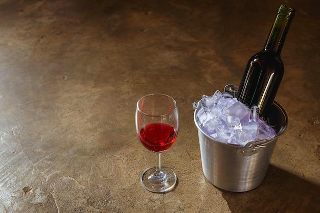 Garrafa de vinho tinto em um balde de gelo e uma taça de vinho tinto