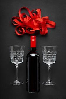 Garrafa de vinho tinto, lindos copos de vinho e uma fita vermelha.