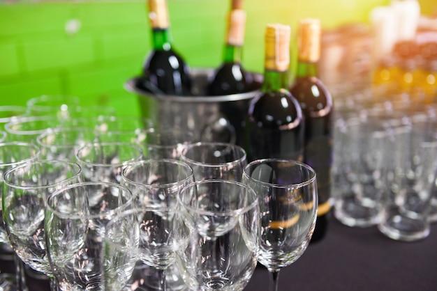 Garrafa de vinho tinto no balde de gelo e copo de vinho no fundo da mesa / copo de champanhe para festa de comemoração