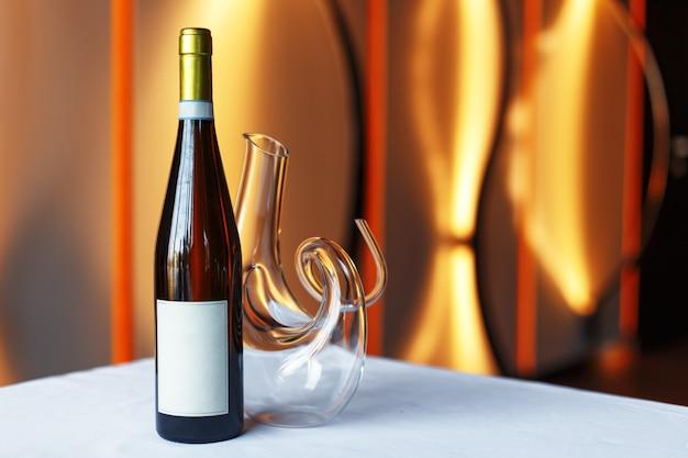 Garrafa de vinho tinto, um copo de vinho e uma jarra sobre uma mesa com uma toalha de mesa branca.