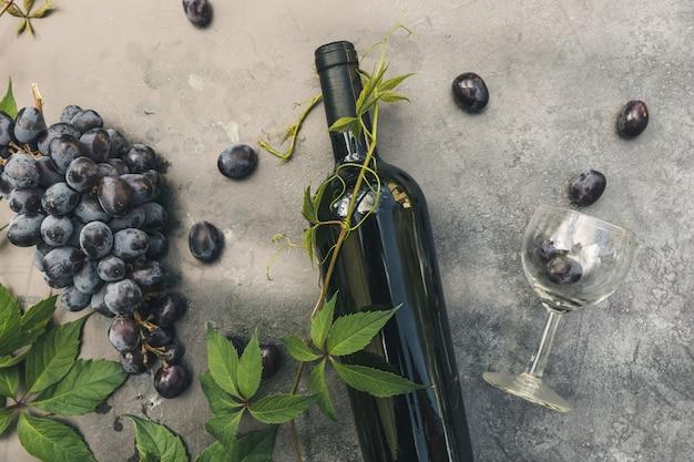 Garrafa de vinho tinto, videira verde, copo de vinho e uva madura no fundo da mesa de pedra escura vintage. espaço de cópia de vista superior para texto. adega de bar de vinhos de loja de vinhos ou conceito de degustação de vinhos.