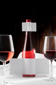 Garrafa de vinho transparente com rótulo em branco e copos