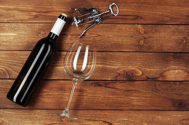 Garrafa de vinho vermelha, copo de vinho e saca-rolhas no fundo da mesa de madeira