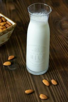 Garrafa de vista lateral com leite em uma mesa com amêndoas