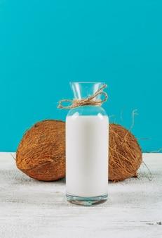 Garrafa de vista lateral de leite com cocos em fundo branco de madeira. horizontal