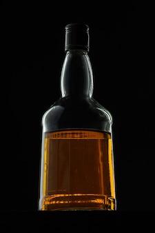 Garrafa de whisky iluminada contra fundo preto escuro
