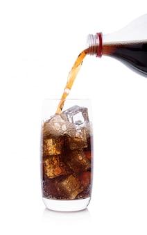 Garrafa derramando cola em copo de bebida com cubos de gelo
