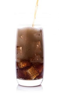 Garrafa derramando cola no copo de bebida com cubos de gelo