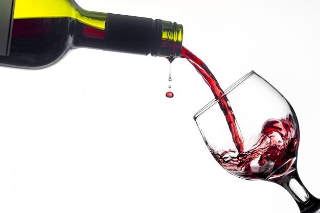 Garrafa derramando vinho em um copo isolado no fundo branco