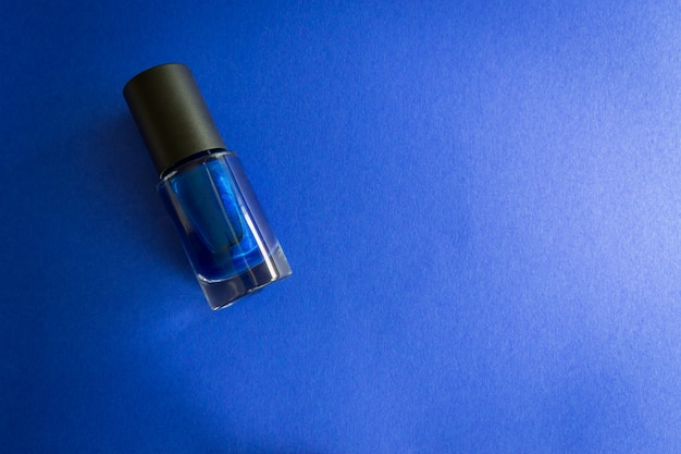 Garrafa do verniz para as unhas no fundo azul. copyspace