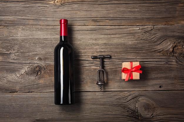 Garrafa do vinho com vidro e caixa de presente de vinho no fundo de madeira. vista superior com espaço de cópia para o seu texto.