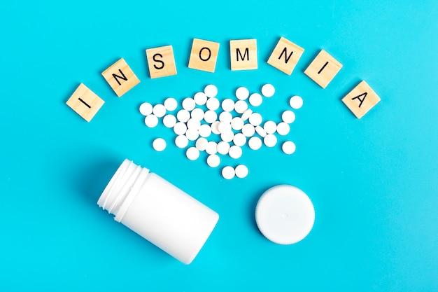 Garrafa e comprimidos brancos em um fundo azul. o conceito de tratamento da insônia.