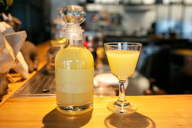 Garrafa e copo cheio de bebida alcoólica amarela no balcão do bar
