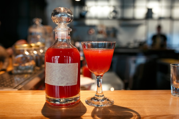 Garrafa e copo cheio de bebida alcoólica vermelha no balcão do bar
