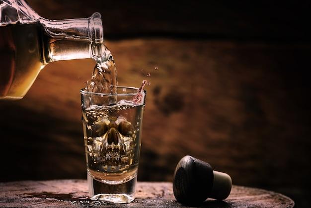 Garrafa e copo com bebida alcoólica, com imagem de caveira de vidro translúcido. conceito de alcoolismo