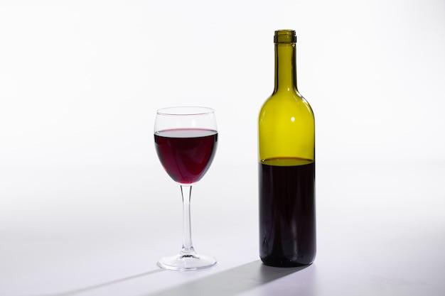 Garrafa e copo com vinho tinto na parede branca