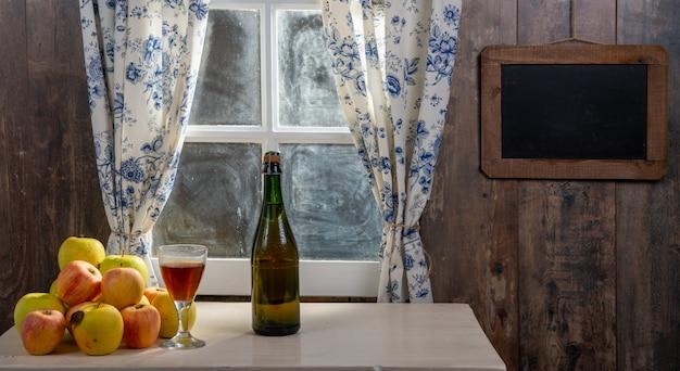 Garrafa e copo de cidra com maçãs. em casa rústica