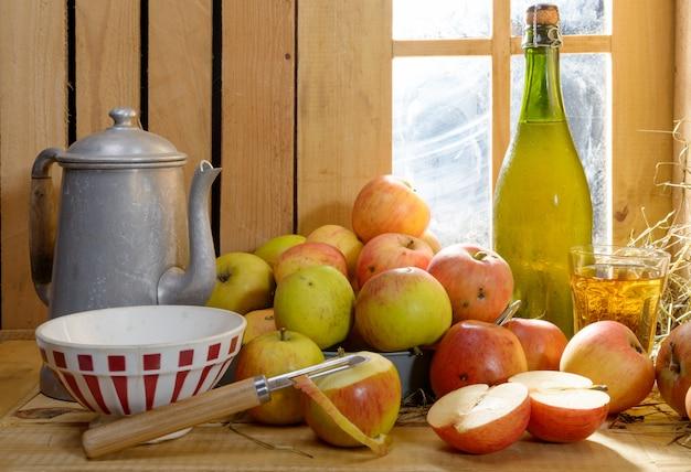 Garrafa e copo de cidra com maçãs