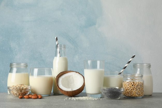 Garrafa e copo de diferentes tipos de leite na mesa cinza