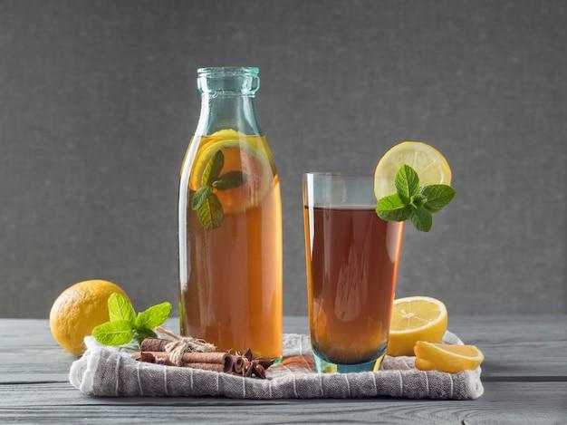 Garrafa e copo de kombucha com limões na mesa de madeira cinza