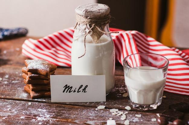 Garrafa e copo de leite com biscoitos na mesa.
