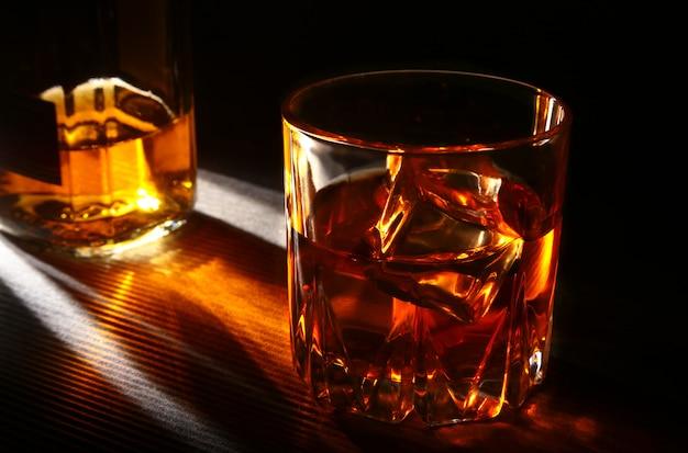 Garrafa e copo de uísque ou bourbon com gelo na mesa de pedra preta.