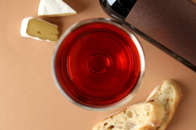 Garrafa e copo de vinho, queijo e pão em fundo bege