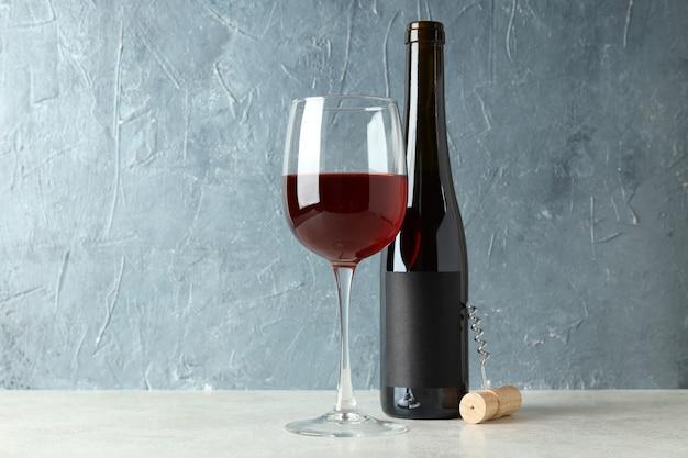 Garrafa e copo de vinho tinto e saca-rolhas contra um fundo azul texturizado