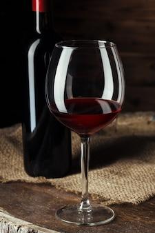 Garrafa e copo de vinho tinto no barril de madeira baleado