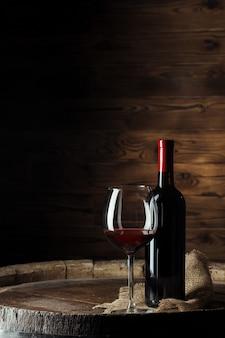 Garrafa e copo de vinho tinto no barril de madeira, tiro com fundo escuro de madeira