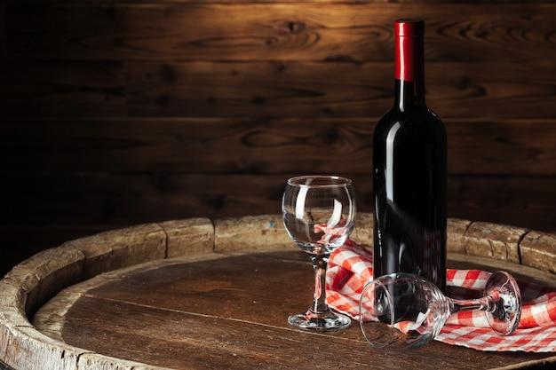 Garrafa e copo de vinho tinto no barril de madeira