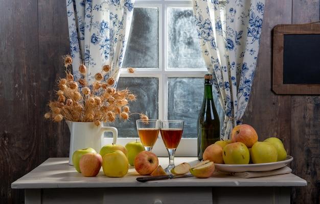 Garrafa e copos de cidra com maçãs, perto da janela, em casa rústica