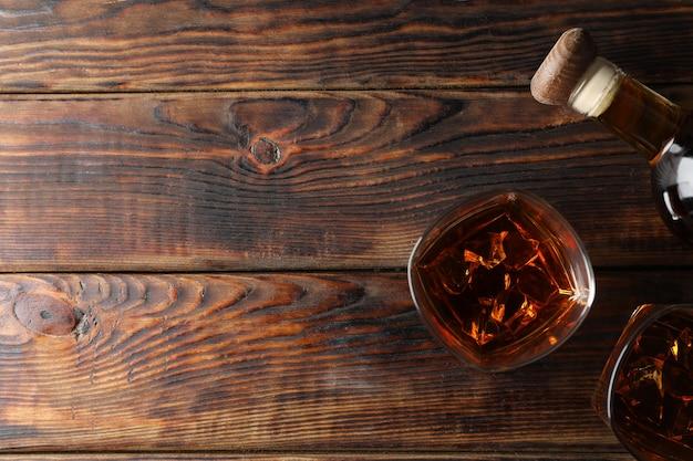 Garrafa e copos de uísque na madeira