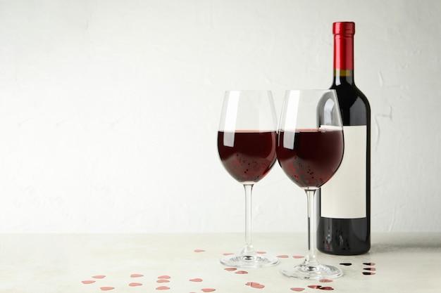Garrafa e copos de vinho tinto na mesa texturizada branca