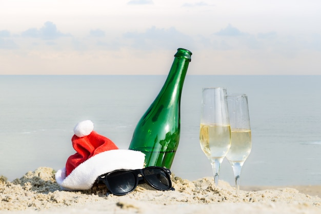 Garrafa e copos na areia na praia do mar