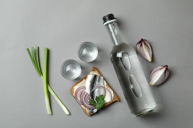 Garrafa e doses de vodka e salgadinhos em fundo cinza
