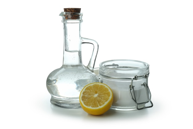 Garrafa e pote de ácido e limão isolados no fundo branco isolado