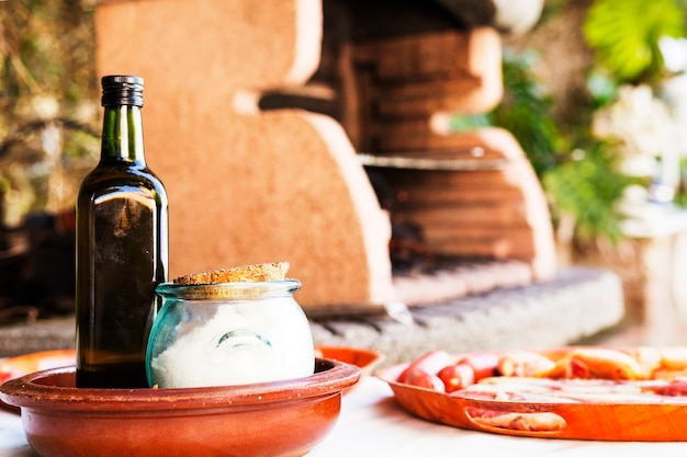 Garrafa e sal jar com variedade de carne na mesa perto do churrasco