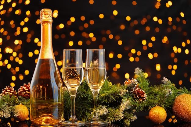 Garrafa e taças de champanhe acesas em luzes desfocadas