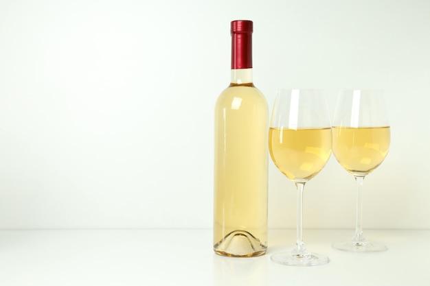 Garrafa e taças de vinho na mesa branca