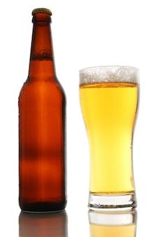 Garrafa e um copo de cerveja com espuma isolado no fundo branco