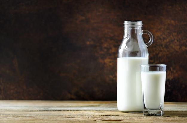 Garrafa e vidro de leite na tabela de madeira, fundo escuro. conceito de alimentação saudável. espaço da cópia