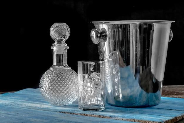 Garrafa e vidro vazios do cubo de gelo no fundo de madeira azul da tabela.