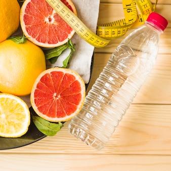Garrafa; fita métrica e frutas cítricas na placa