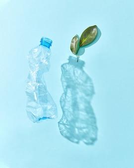 Garrafa flutuante de plástico com sombras e galho de planta verde em uma parede azul pastel, copie o espaço. poluição ambiental do plástico.