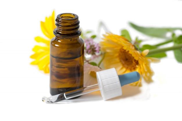 Garrafa marrom com flores de calêndula e camomila