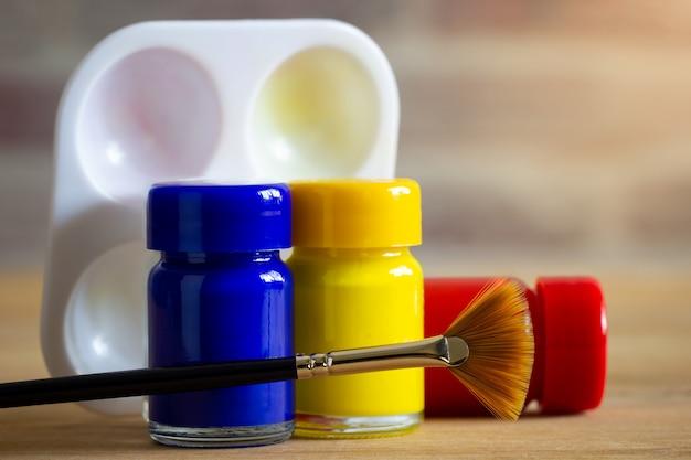Garrafa, pincel e paleta da cor do cartaz na tabela de madeira com fundo da parede de tijolo e luz solar da manhã.