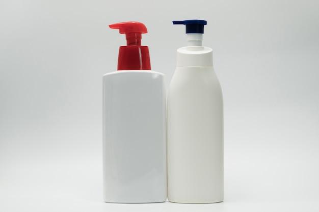 Garrafa plástica branca cosmética com o distribuidor azul e vermelho da bomba isolado no fundo branco com espaço vazio da etiqueta e da cópia. frasco de cuidados com a pele. loção para o corpo. pacote de frasco cosmético. frasco de xampu.