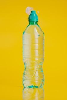 Garrafa plástica de água mineral em um fundo amarelo brilhante